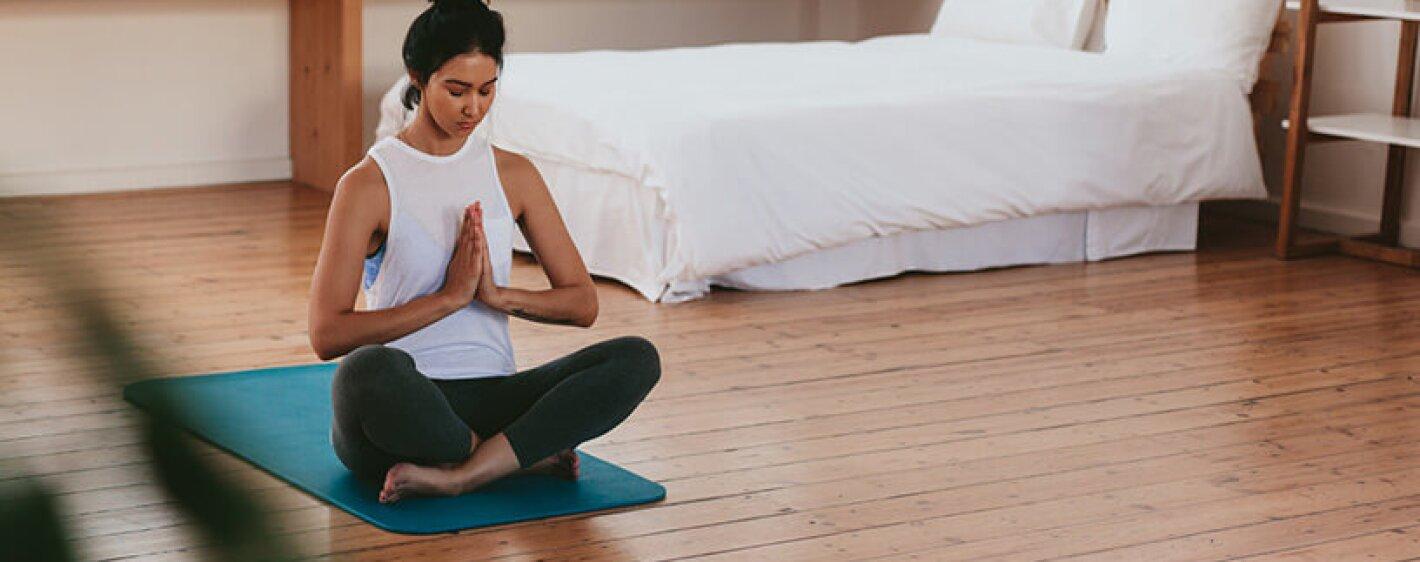 woman namasté on yoga mat