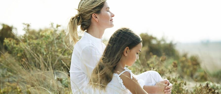 mother and daughter beach meditation