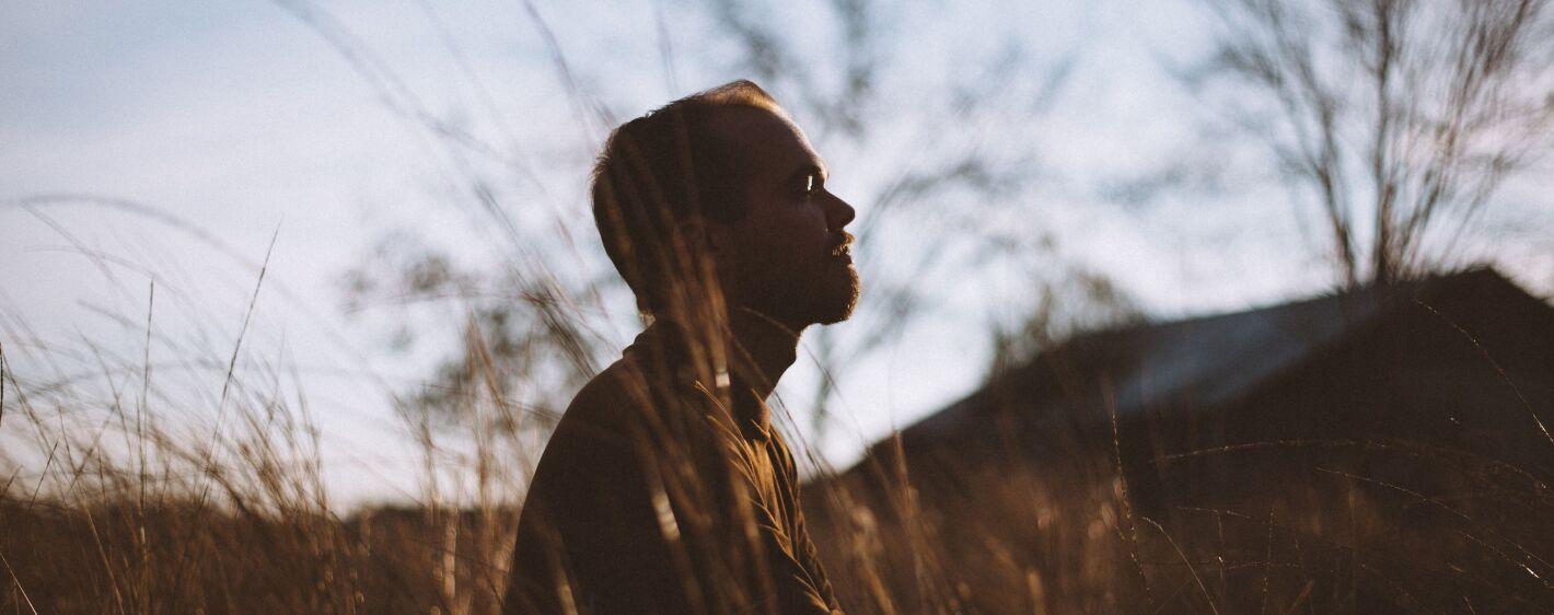 Man in field meditating