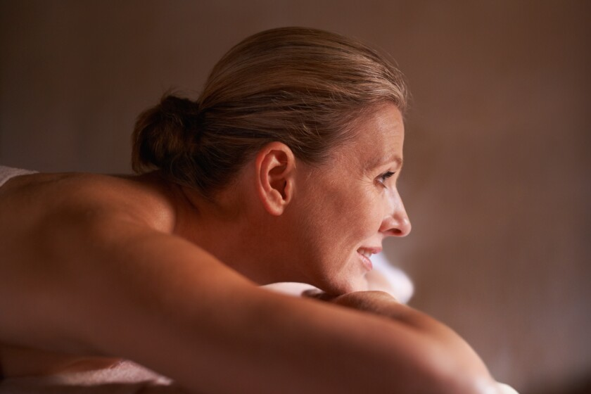 Cropped shot of a woman in a day spa relaxing on a massage table