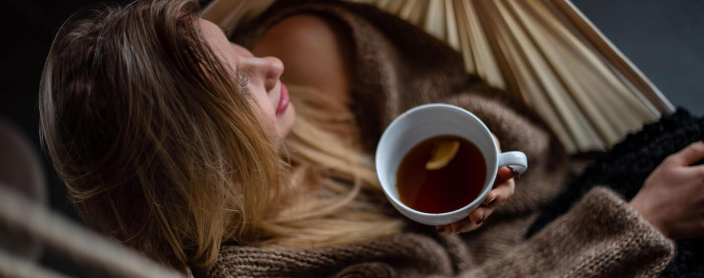 Person resting in a hammock with a cup of tea