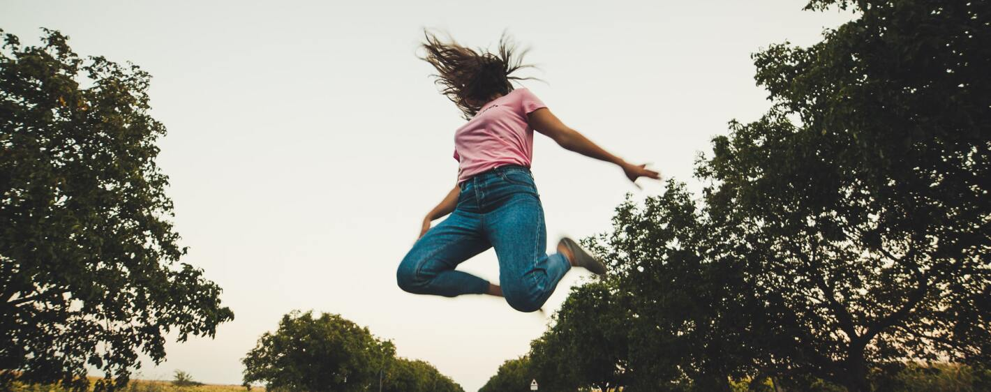 Girl in pink top jumping in the street