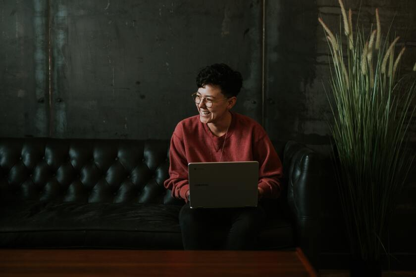 A young woman sitting on a couch with a laptop