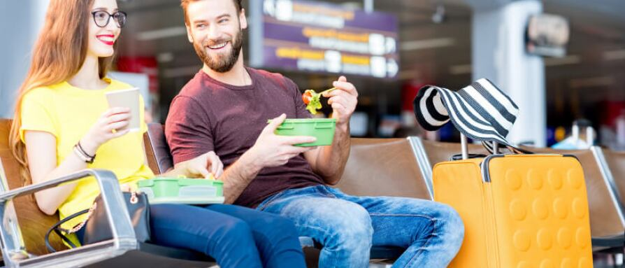 man and woman eating at the airport