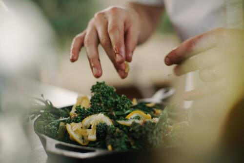 A close up of a woman preparing broccolini with lemon