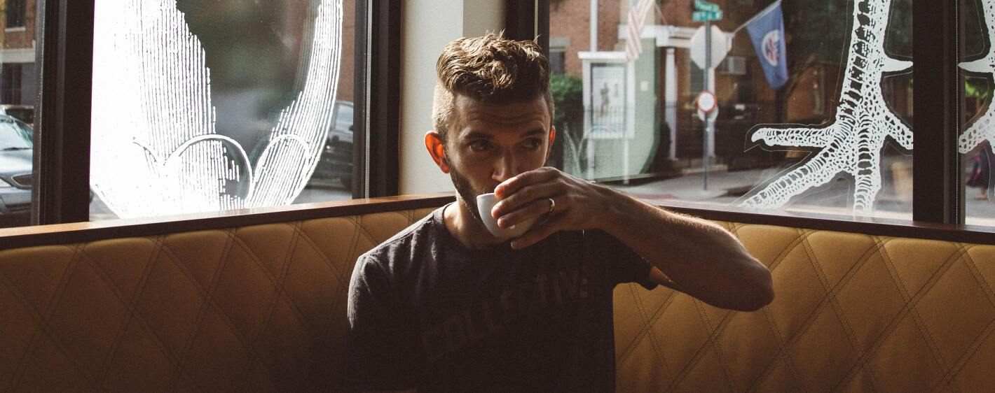 Guy drinking hot tea in a cafe