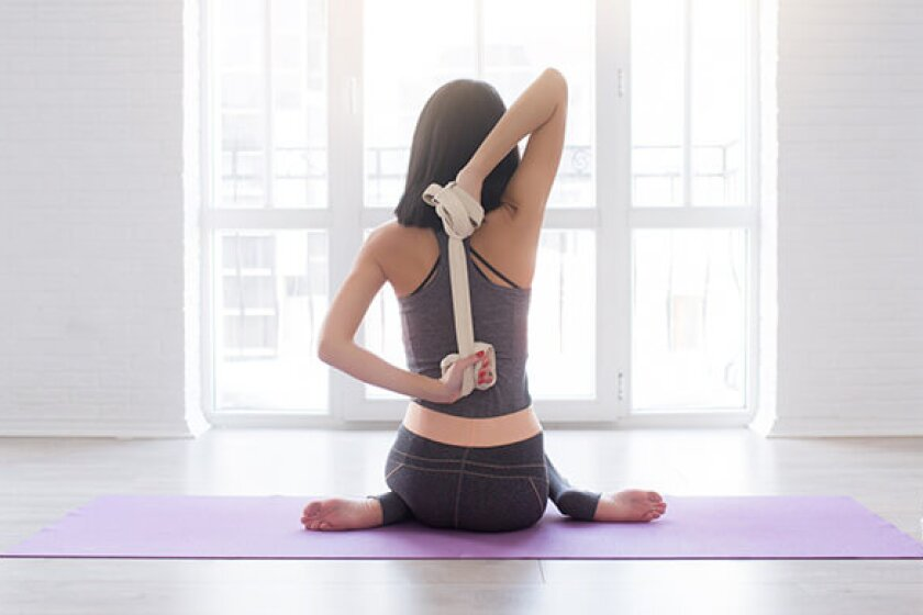 Woman stretching with yoga straps