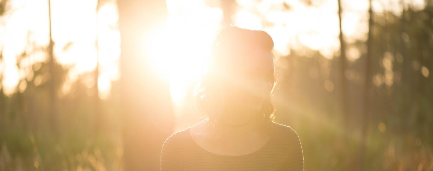 A smiling young woman at sunrise