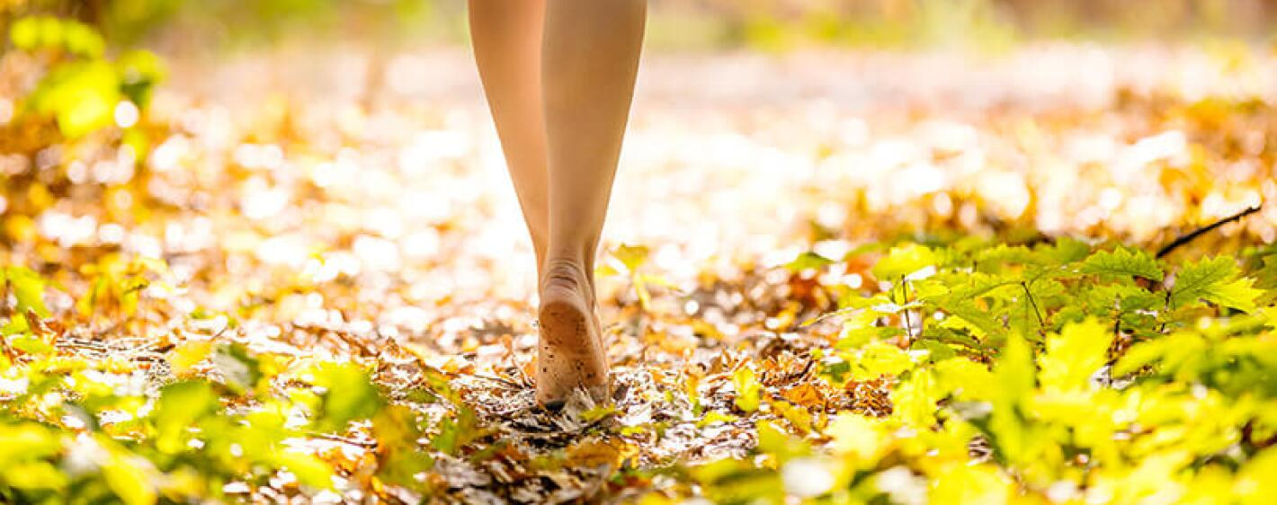 Woman walking barefoot in the forest