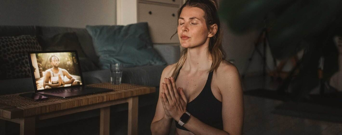 A young woman meditating in prayer pose