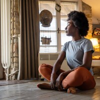 Portrait of peaceful young black woman meditating indoors