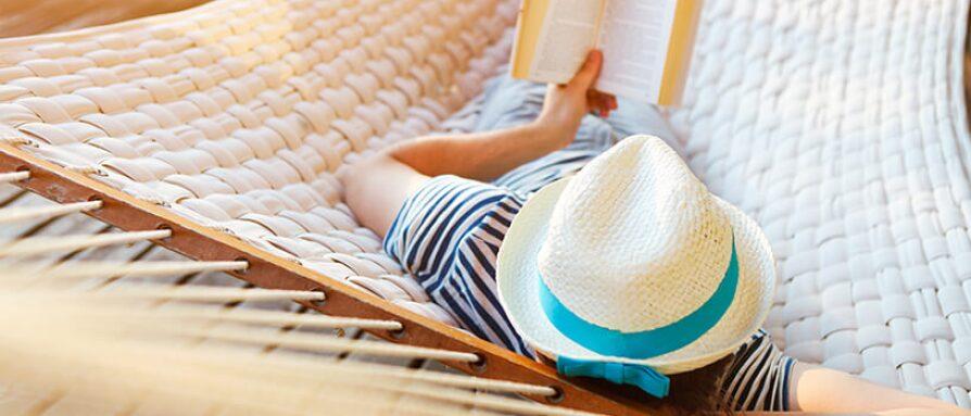 man relaxing reading in hammock