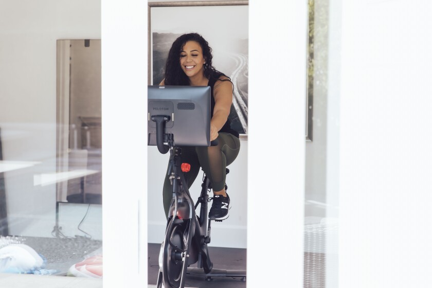 A happy young woman on an exercise bike
