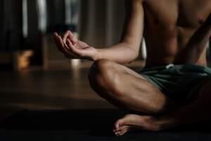 Man in shorts sitting on lotus meditation pose