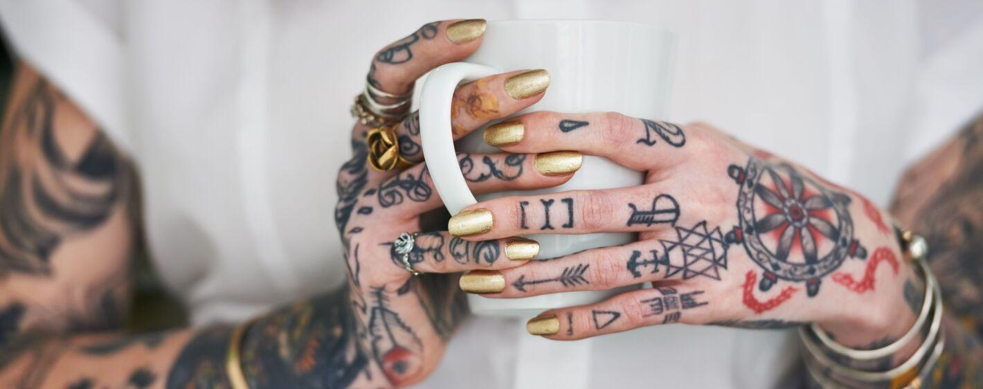 Tattoo woman holding coffee mug