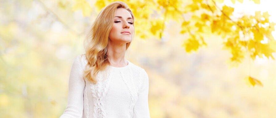 Woman meditating under an autumn tree