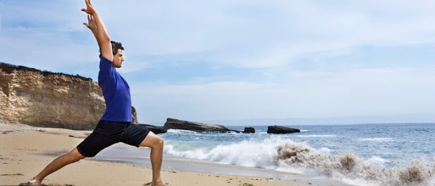 A man doing yoga on the beach