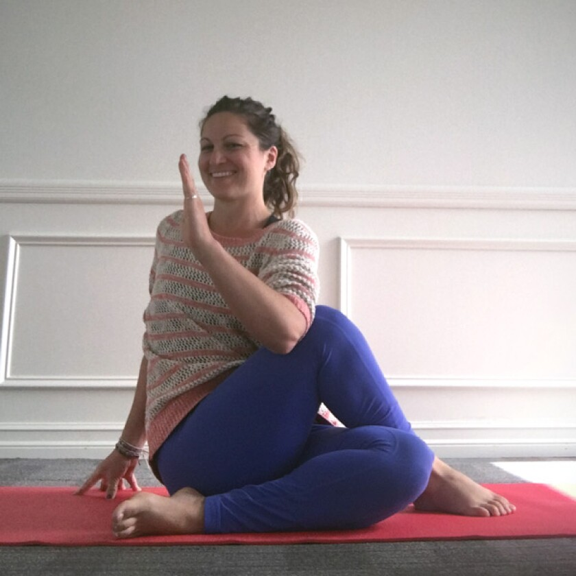Yoga teacher in seated spinal twist