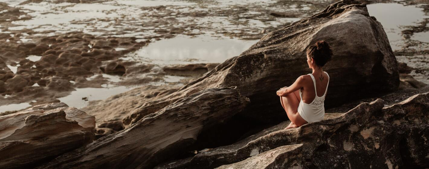 Woman sitting on rock at the beach