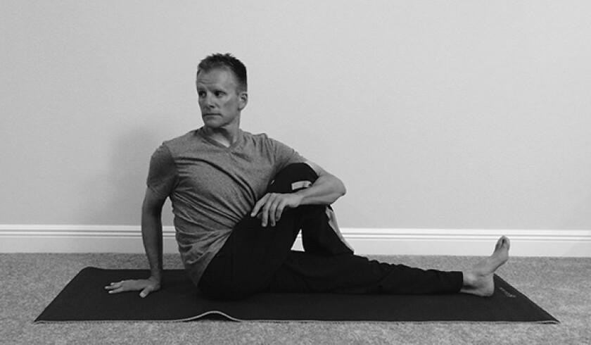 Man in seated twist yoga pose