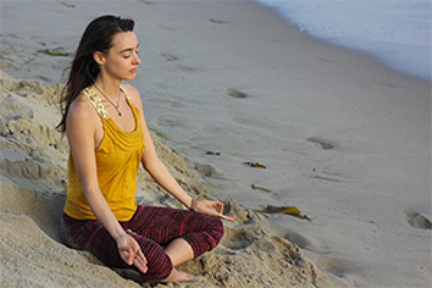 Woman practicing pranayama at the beach