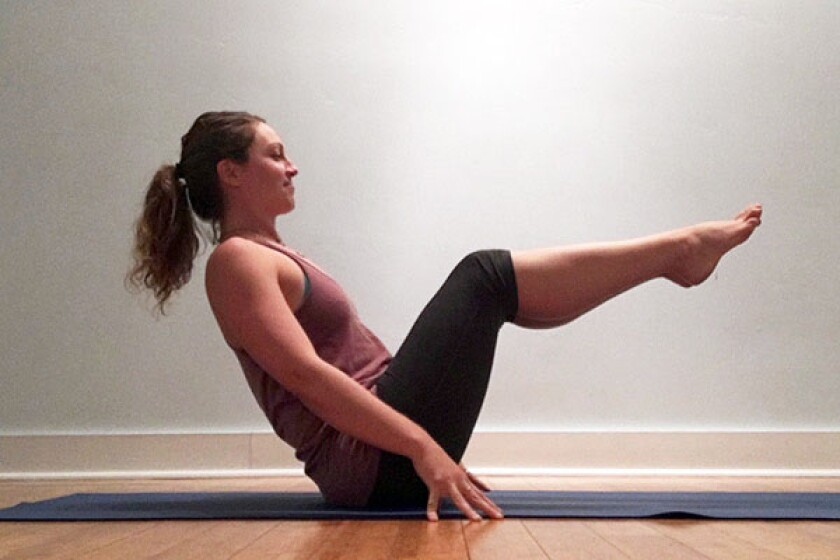 Yoga teacher in supported boat pose
