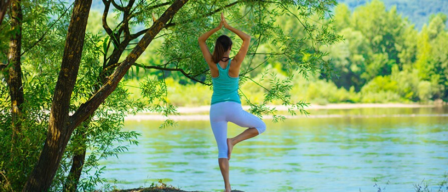 Woman in yoga tree pose by a lake