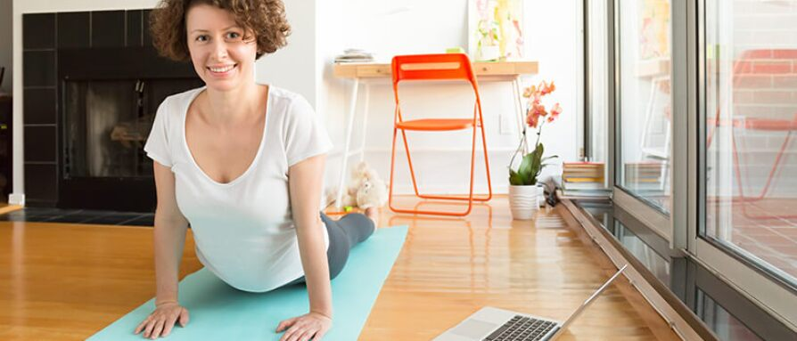 woman doing yoga with laptop