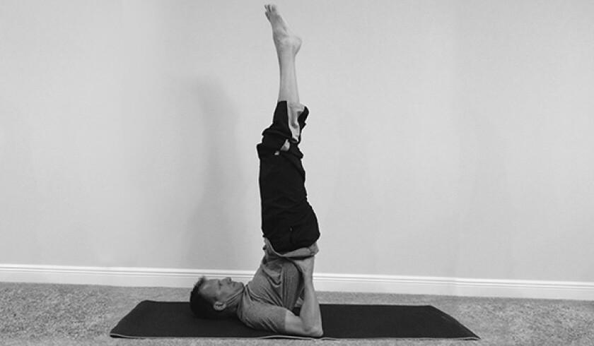 Man in shoulder stand yoga pose
