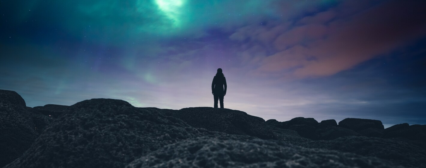 Person standing on mountain looking at colorful night sky