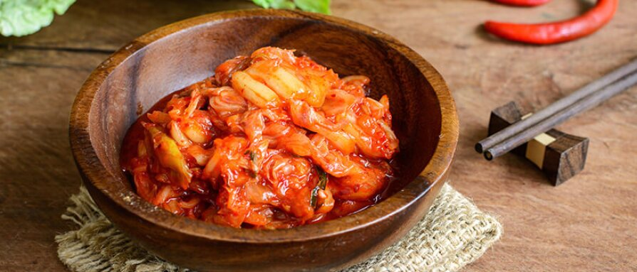 A bowl of fermented kimchi with chopsticks on a wooden table