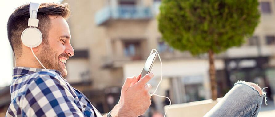 A man listening to a podcast on his phone with headphones