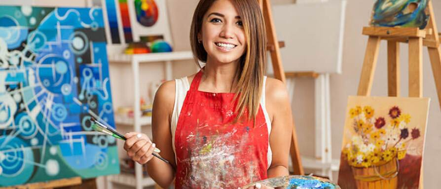 girl smiling with paintbrushes