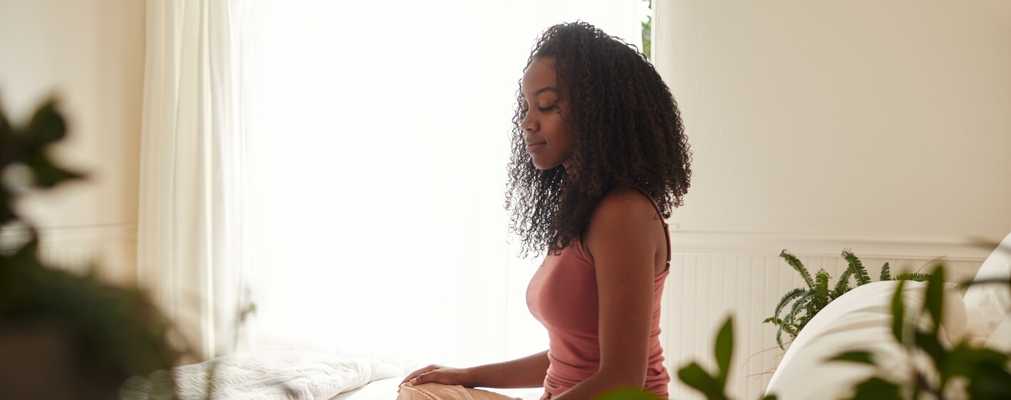 Young woman meditating in her room in the morning