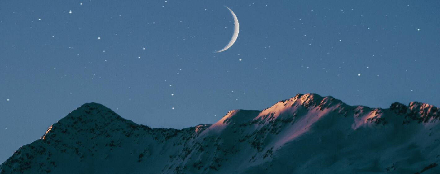 Moon over snowcapped mountains
