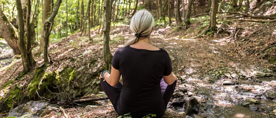 woman meditating hiking trail woods