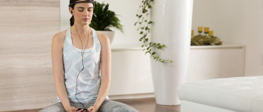 Woman meditating with Muse meditation gadget