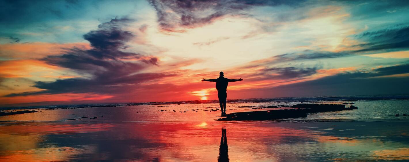 A man enjoying the beach at sunset