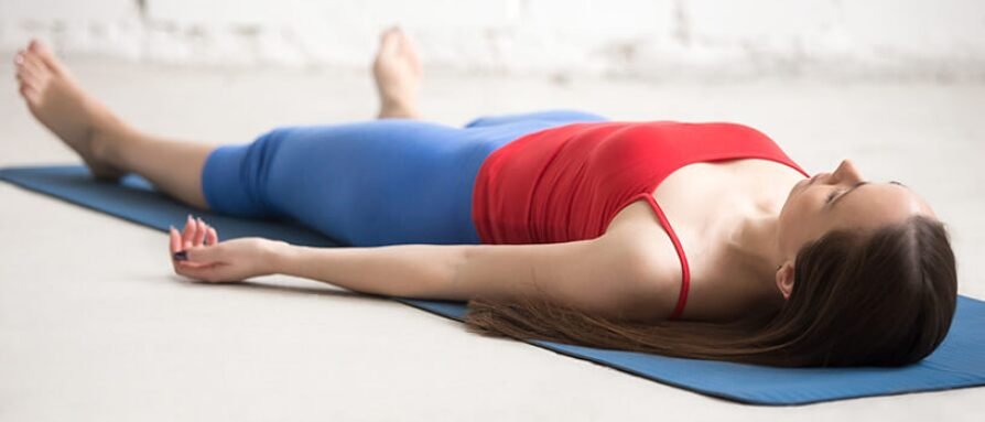 Woman laying on a yoga mat in savasana pose