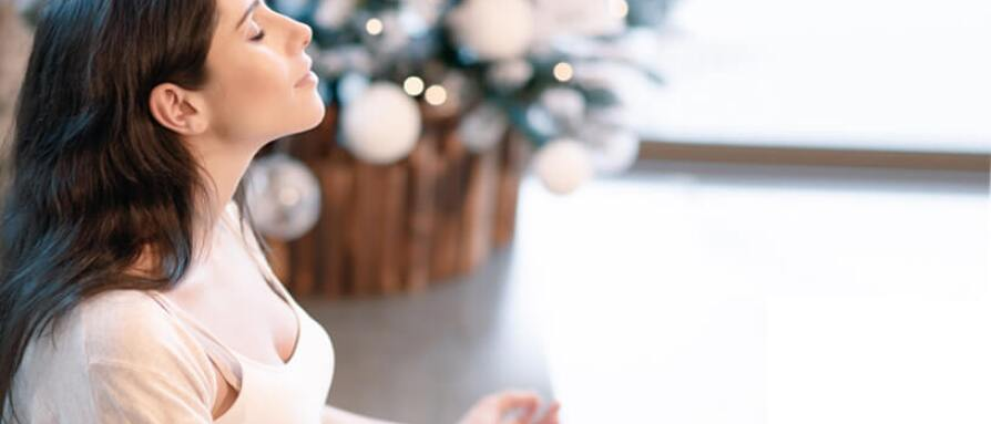 A woman meditating next to a Christmas tree to relieve holiday stress