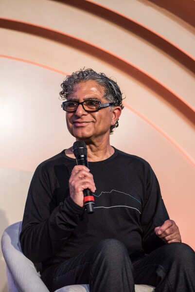Deepak Chopra sitting on a chair and smiling
