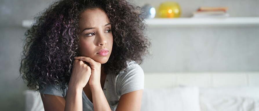 young stressed woman sitting on bed