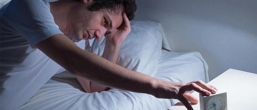 A man suffering from insomnia in bed