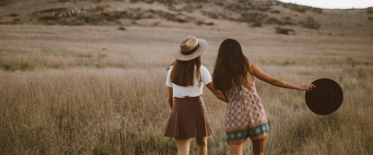 Girls holding hands walking in a field