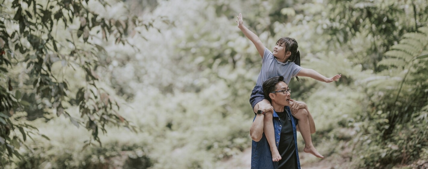 A parent carrying a child on their shoulders along a wooded path