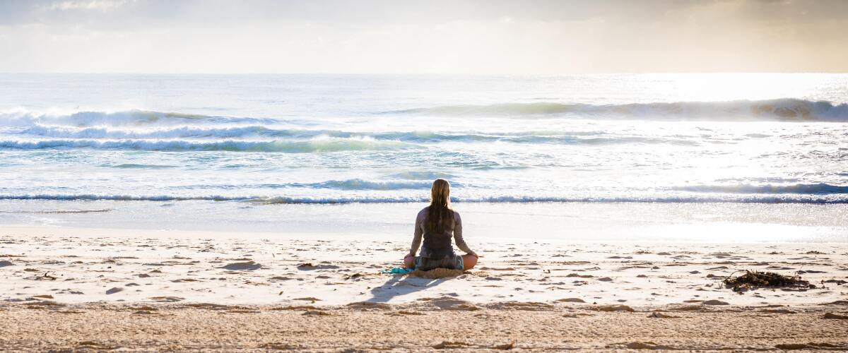 Surfer seated at edge of the water on a sandy beach