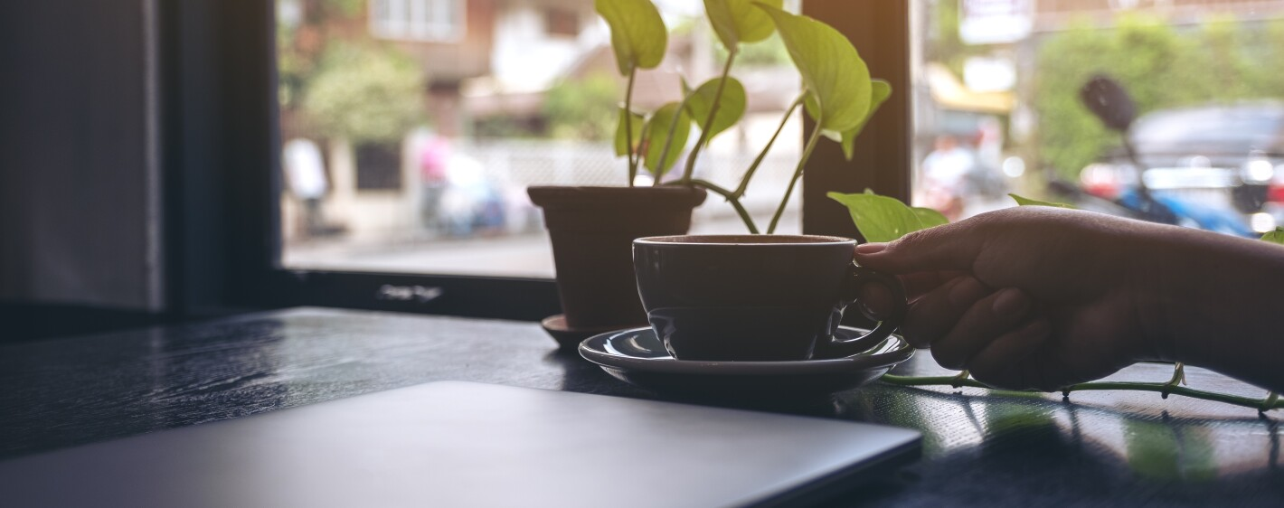 Closeup image of a woman's hand holding a cup of coffee with computer laptop and small tree pot on wooden table