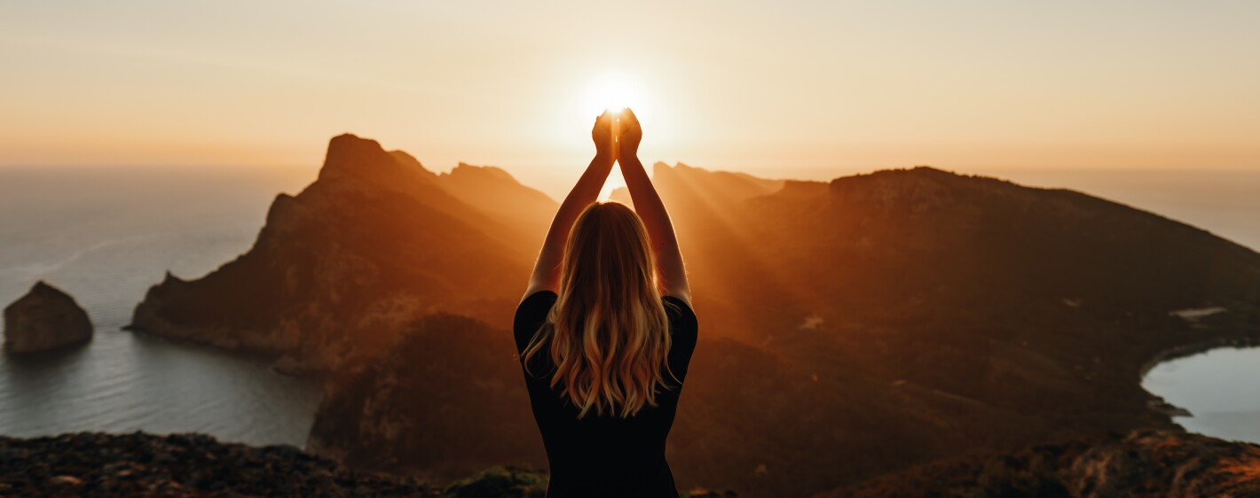 Young woman in spiritual pose holding the light