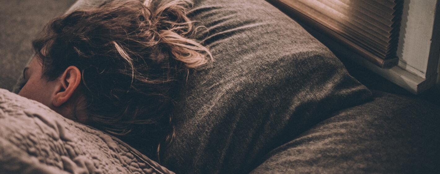 A woman curled up in bed