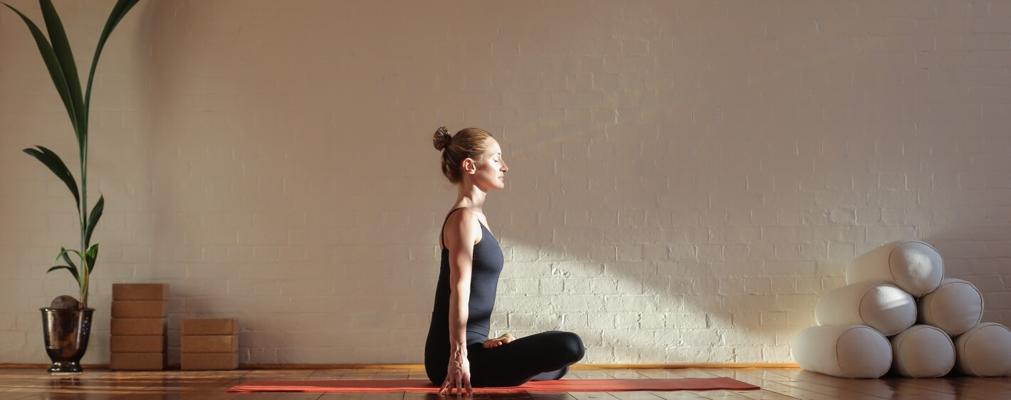 Woman practicing yoga and meditation in a yoga studio